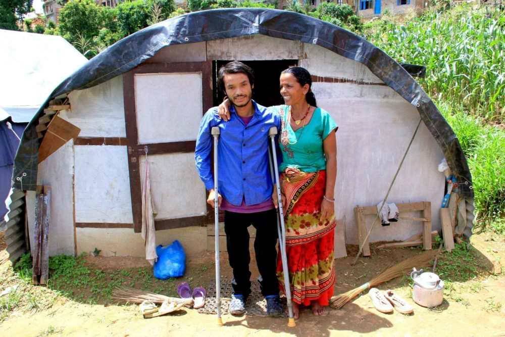 Rajesh, 27, and his mother outside their shelter in Nepal